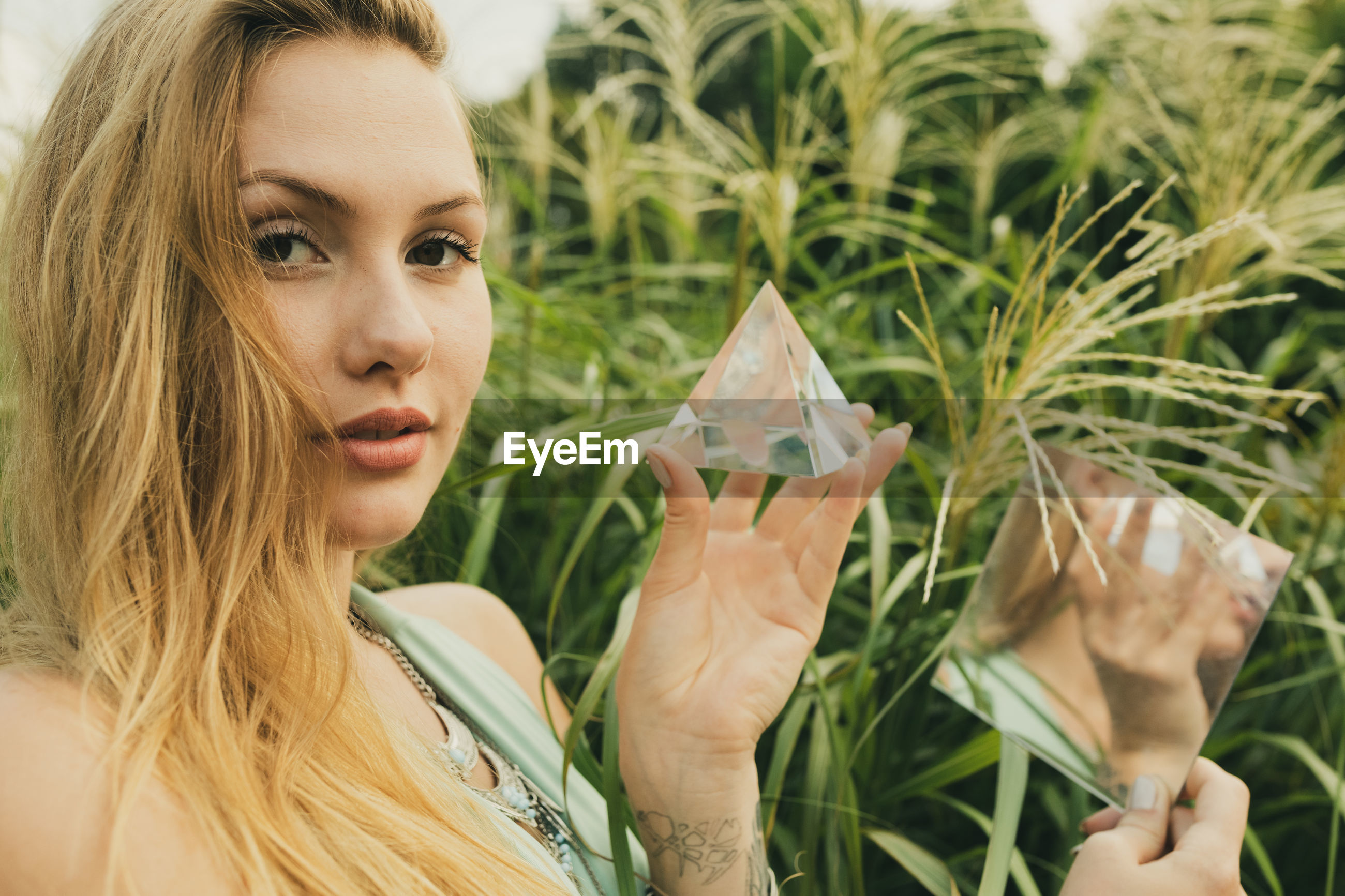 Portrait of young woman holding prism and mirror while standing against plant