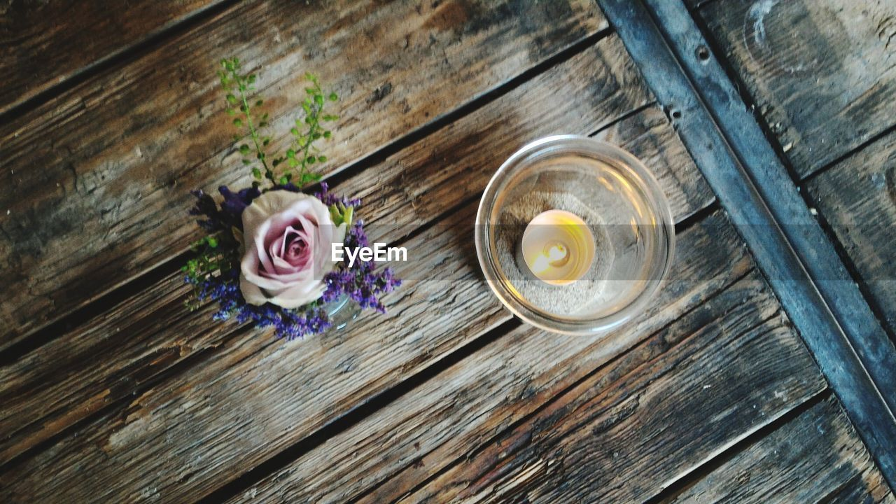 High Angle View Of Flowers With Lit Tea Light Candle On Table
