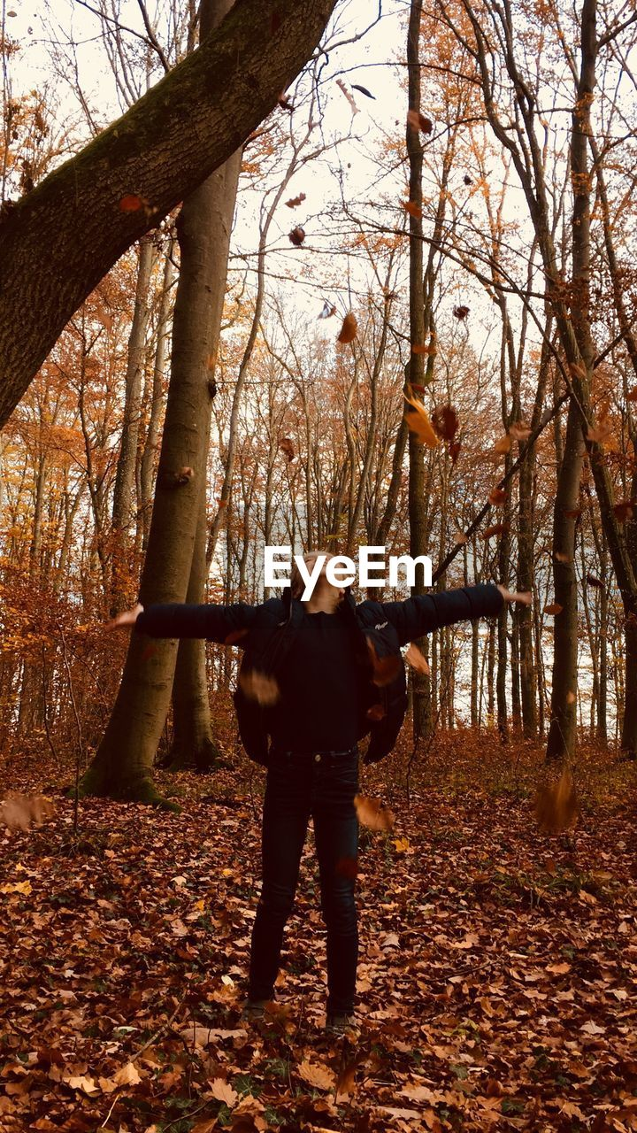 tree, one person, forest, autumn, real people, land, standing, plant, lifestyles, leisure activity, nature, leaf, full length, plant part, change, tree trunk, trunk, day, woodland, rear view, outdoors, human arm, warm clothing, leaves