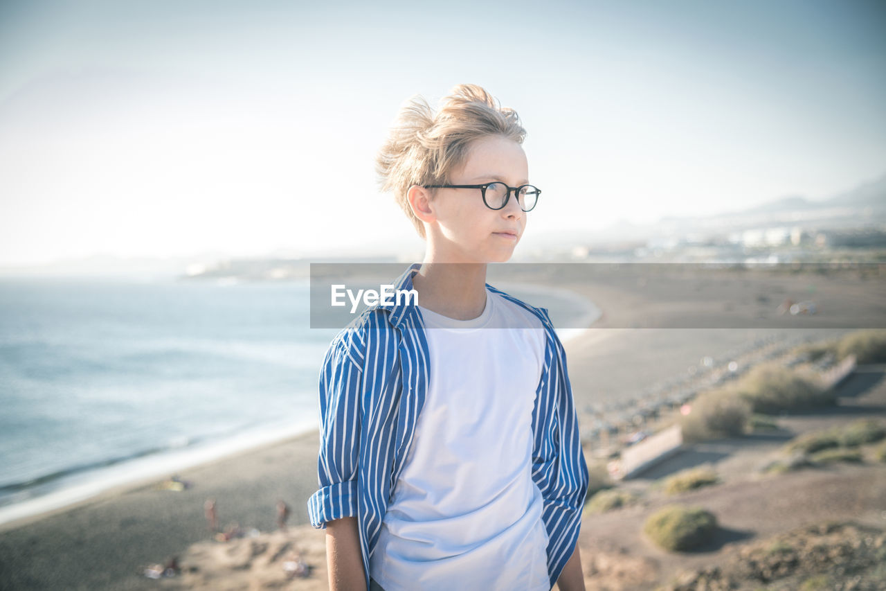 Thoughtful boy standing at beach against sky