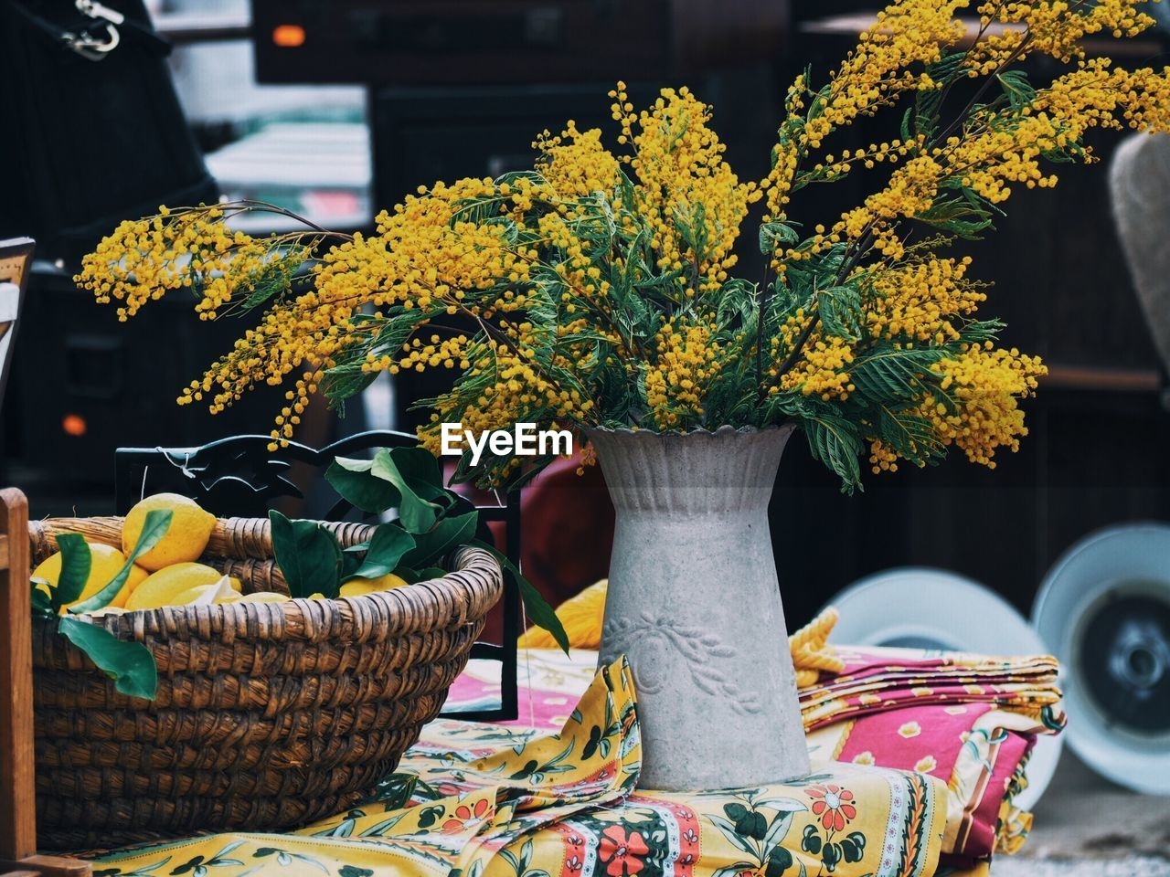plant, flower, flowering plant, freshness, nature, focus on foreground, beauty in nature, growth, no people, vulnerability, table, fragility, day, leaf, plant part, yellow, basket, close-up, decoration, potted plant, outdoors, flower head, flower arrangement, flower pot, bouquet