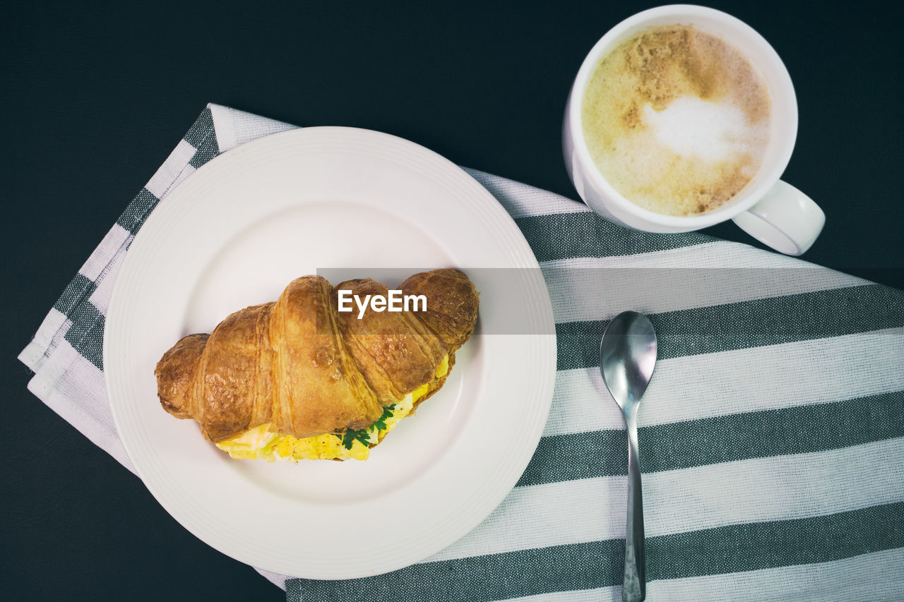 food and drink, cup, food, coffee, coffee - drink, mug, coffee cup, still life, freshness, eating utensil, ready-to-eat, table, kitchen utensil, refreshment, spoon, drink, indoors, high angle view, plate, no people, breakfast, meal, crockery, frothy drink, bun, french food, snack, temptation, black background