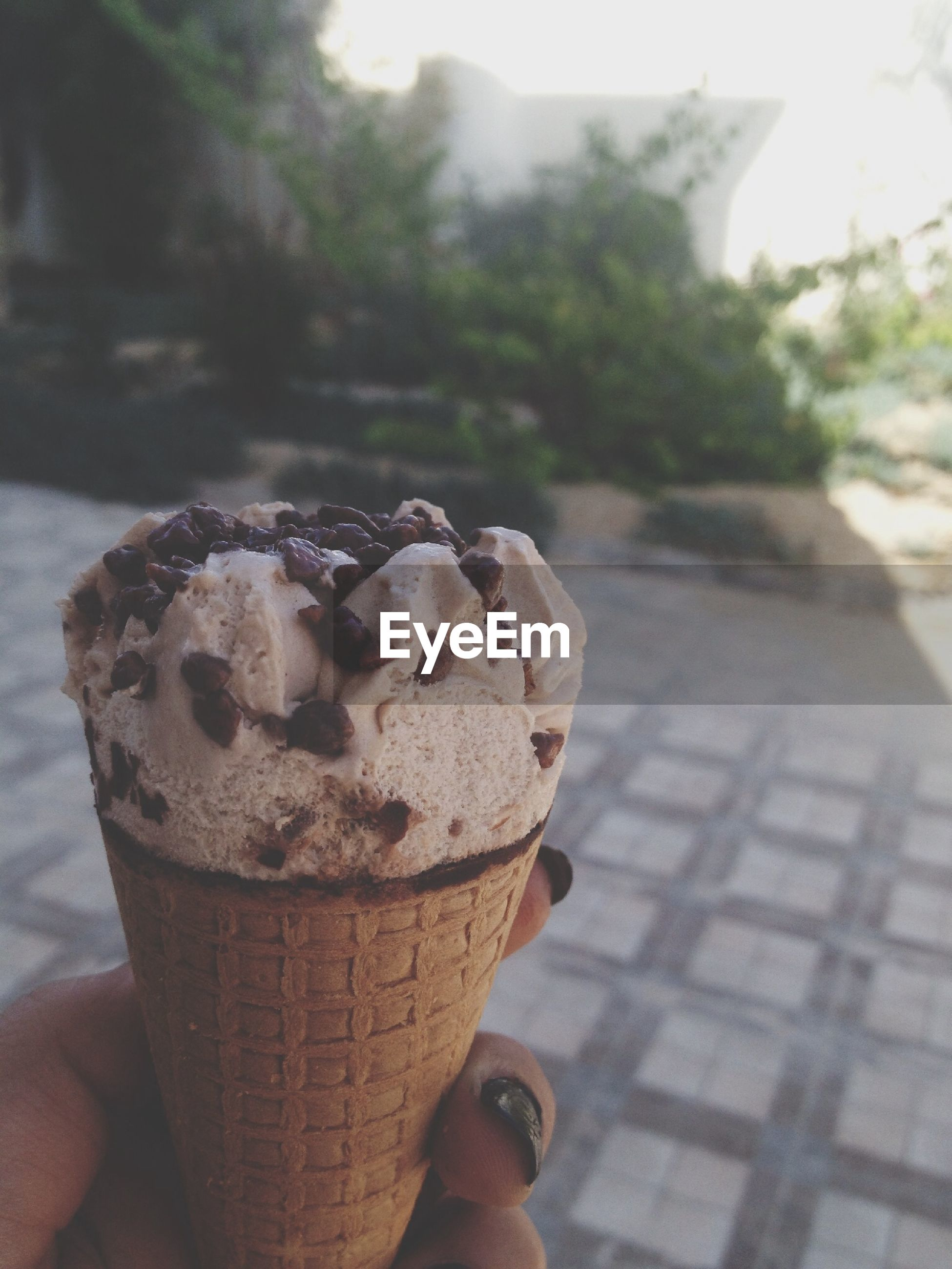 person, focus on foreground, part of, holding, cropped, close-up, sweet food, personal perspective, unrecognizable person, human finger, freshness, food and drink, indulgence, unhealthy eating, dessert, food, ice cream