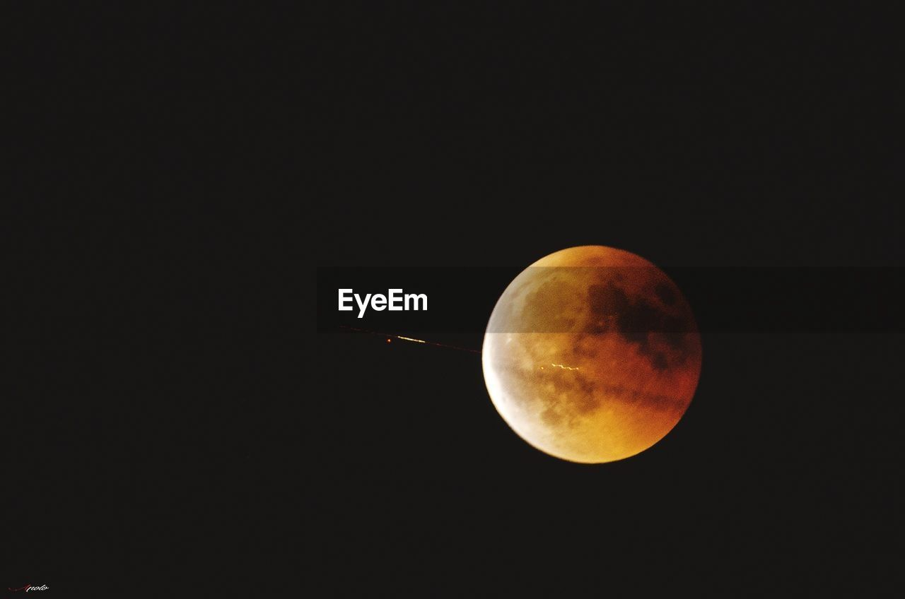 space, astronomy, sky, moon, night, beauty in nature, circle, geometric shape, scenics - nature, copy space, planetary moon, shape, nature, tranquility, moon surface, orange color, no people, clear sky, tranquil scene, low angle view, full moon, outdoors, eclipse, space and astronomy
