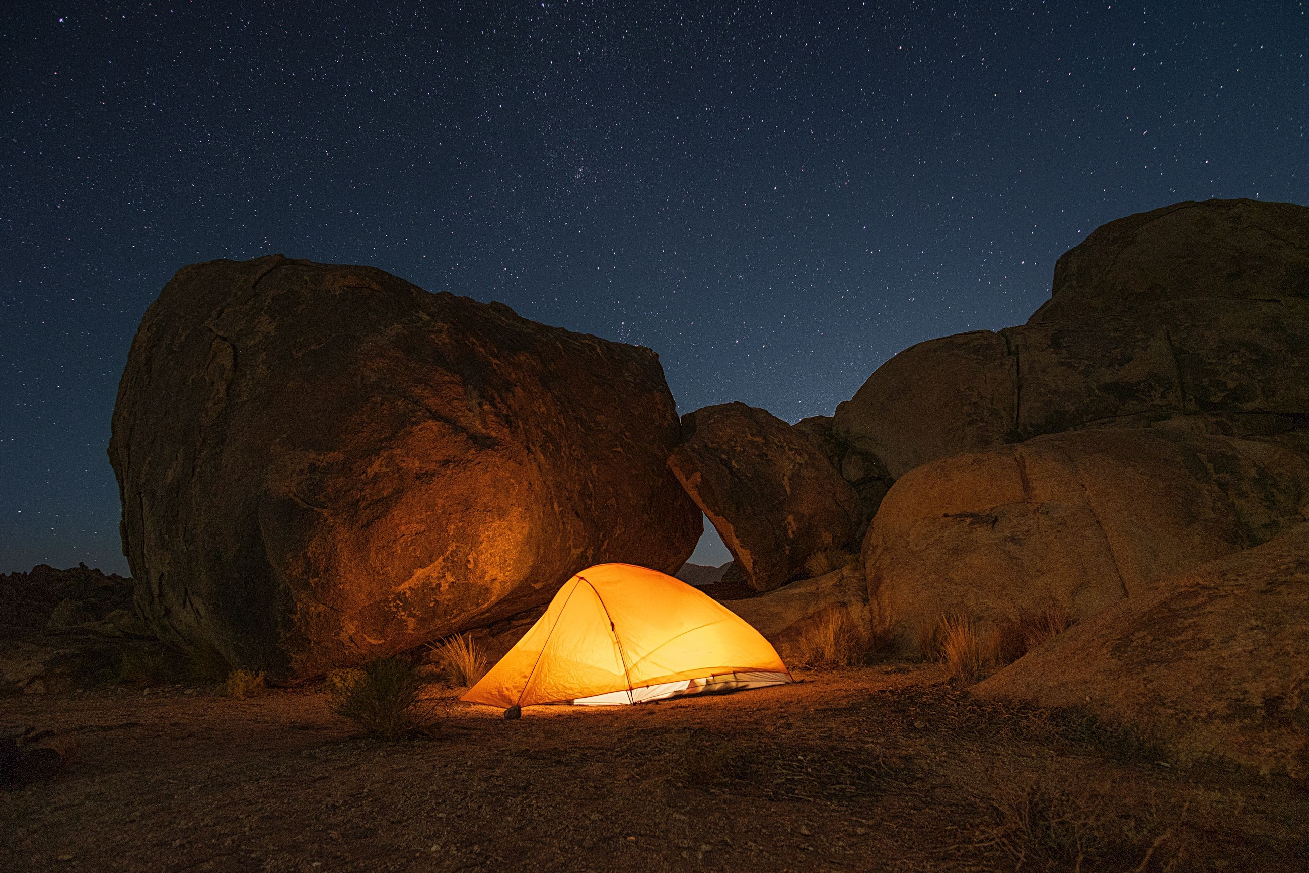 Illuminated tent by rock formations against star field sky