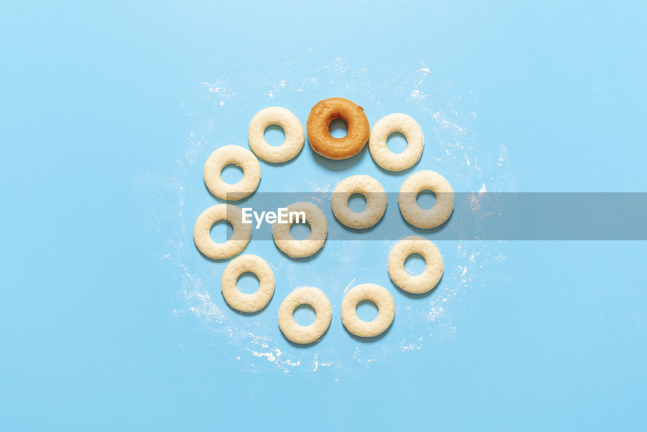 HIGH ANGLE VIEW OF COOKIES IN CONTAINER AGAINST BLUE BACKGROUND