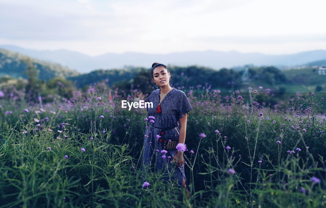 Woman standing amidst plants on field against sky