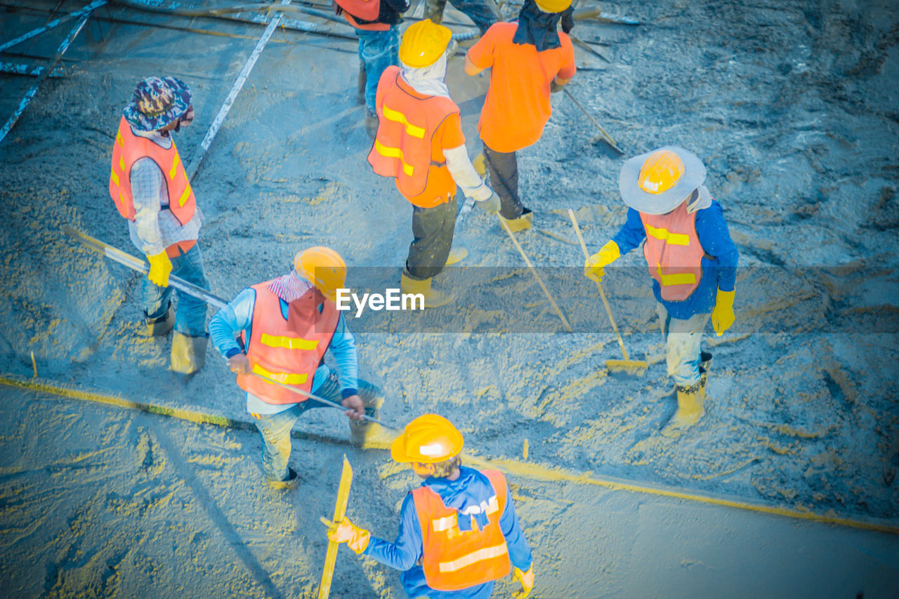 group of people, high angle view, cooperation, teamwork, safety, working, reflective clothing, protection, security, headwear, standing, occupation, hardhat, men, males, clothing, coworker, full length, adult, hat, mature men, mature adult