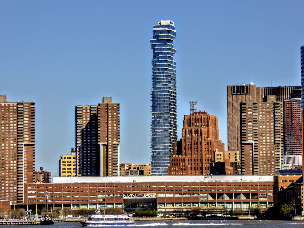 architecture, skyscraper, building exterior, built structure, tall - high, city, modern, outdoors, cityscape, day, no people, bridge - man made structure, clear sky, tall, urban skyline, sky