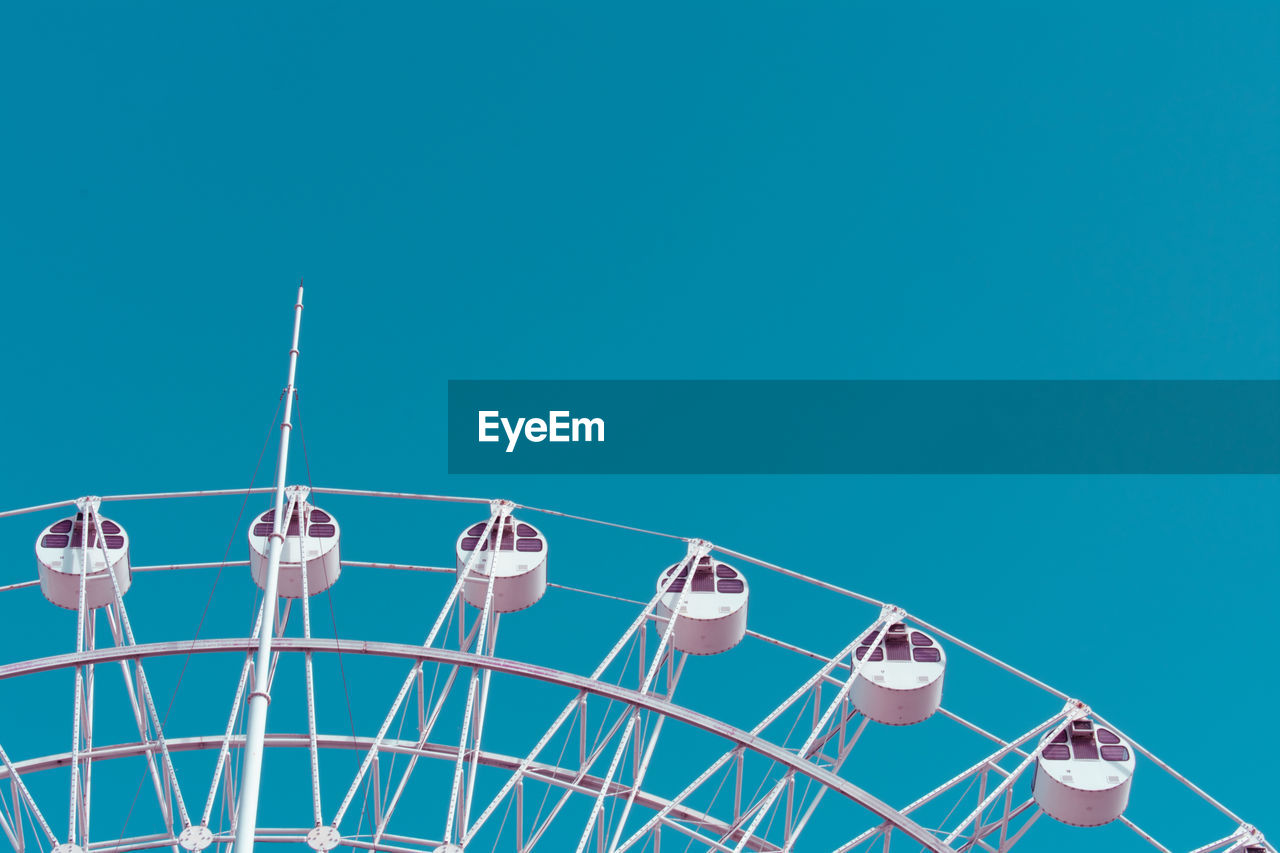 amusement park, amusement park ride, arts culture and entertainment, sky, ferris wheel, copy space, blue, nature, clear sky, low angle view, day, no people, leisure activity, outdoors, sunlight, metal, side by side, transportation, mode of transportation, fun, fairground, wheel, turquoise colored