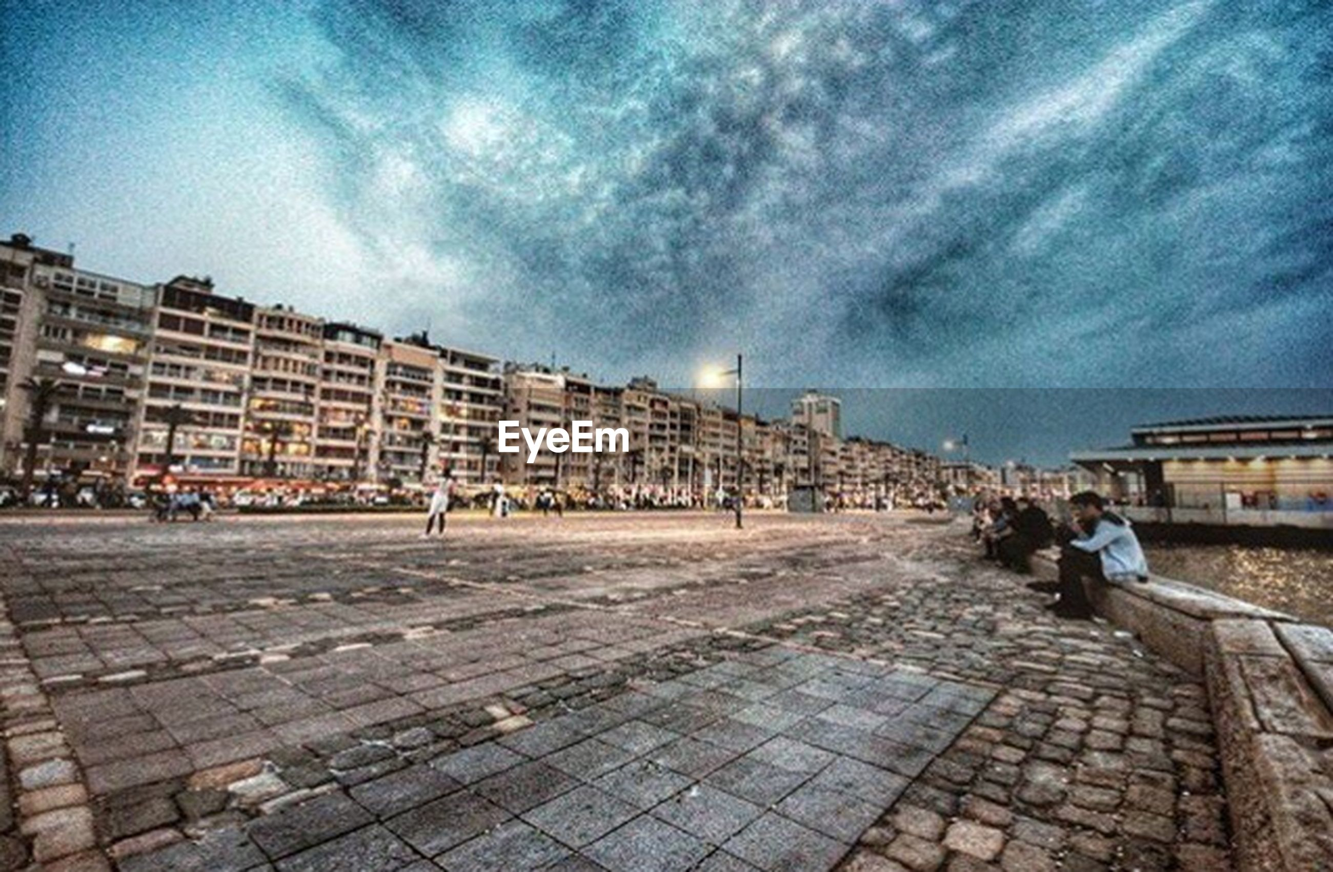 architecture, building exterior, built structure, sky, city, incidental people, cloud - sky, travel destinations, paving stone, day, outdoors, cloudy, development, city life, in front of, surface level, footpath