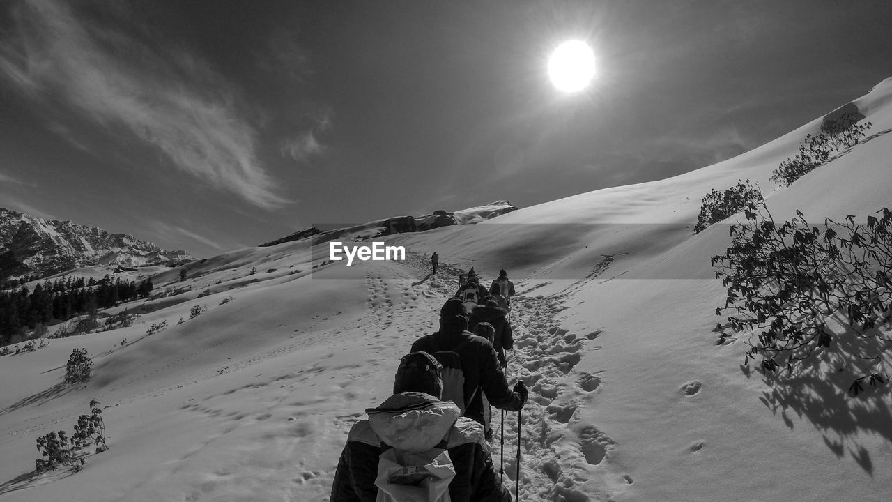 People climbing on snowcapped mountain