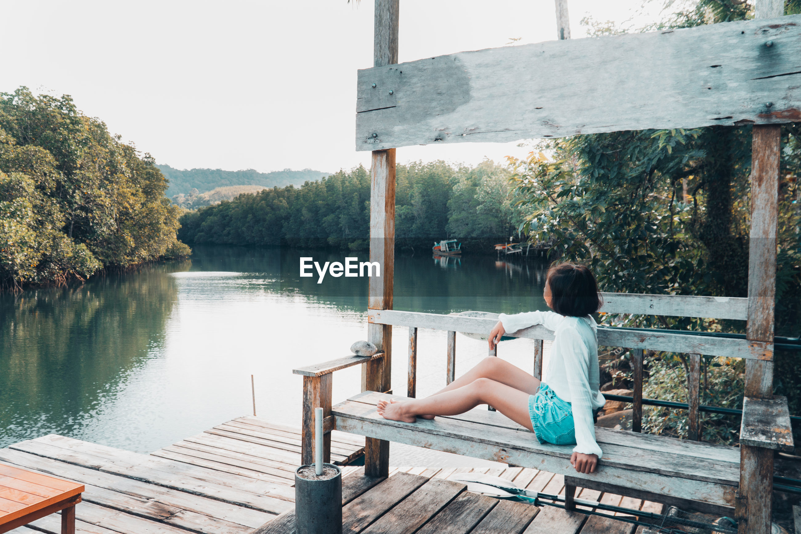 Girl looking at lake against trees