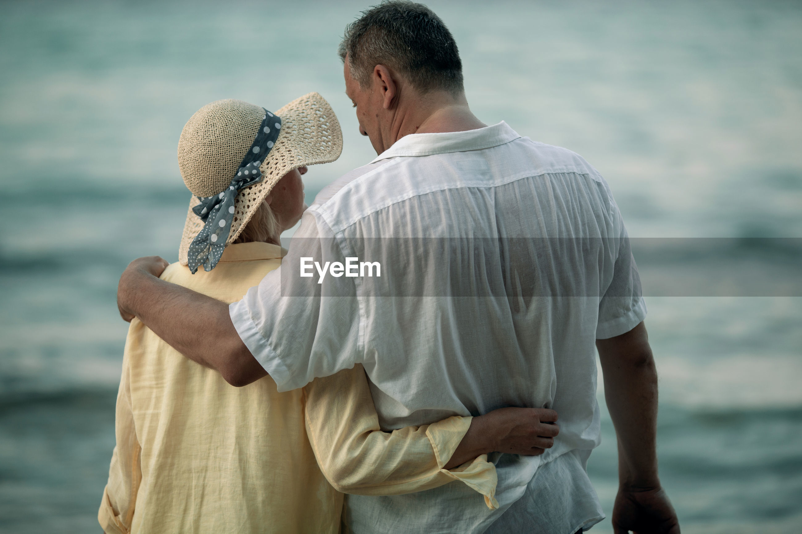Rear view of mature couple standing at beach