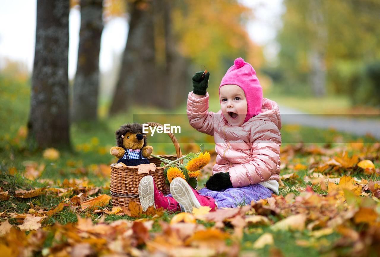 Girl Sitting On Autumn Leaves