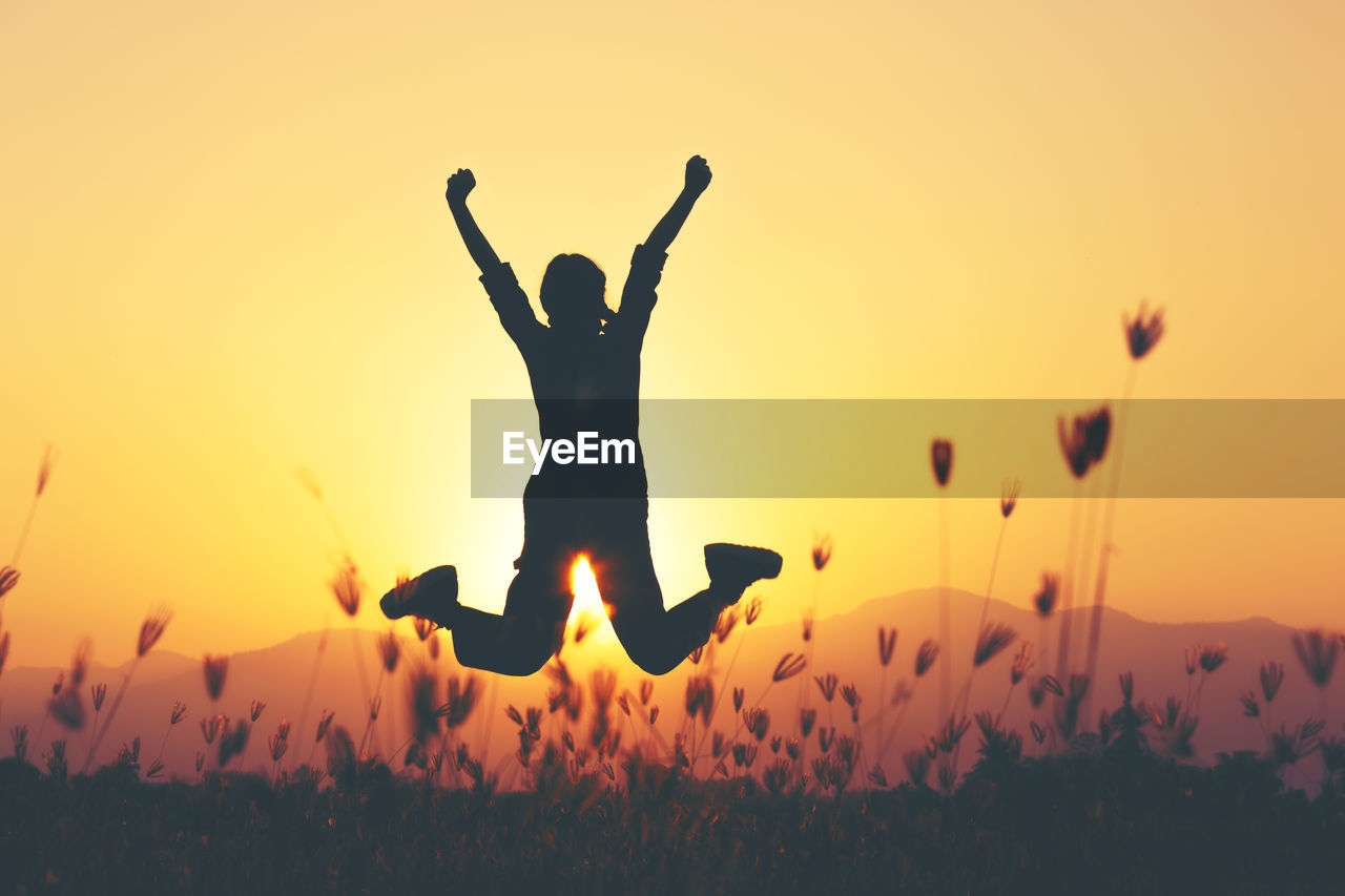 Silhouette woman jumping over field against sky during sunset