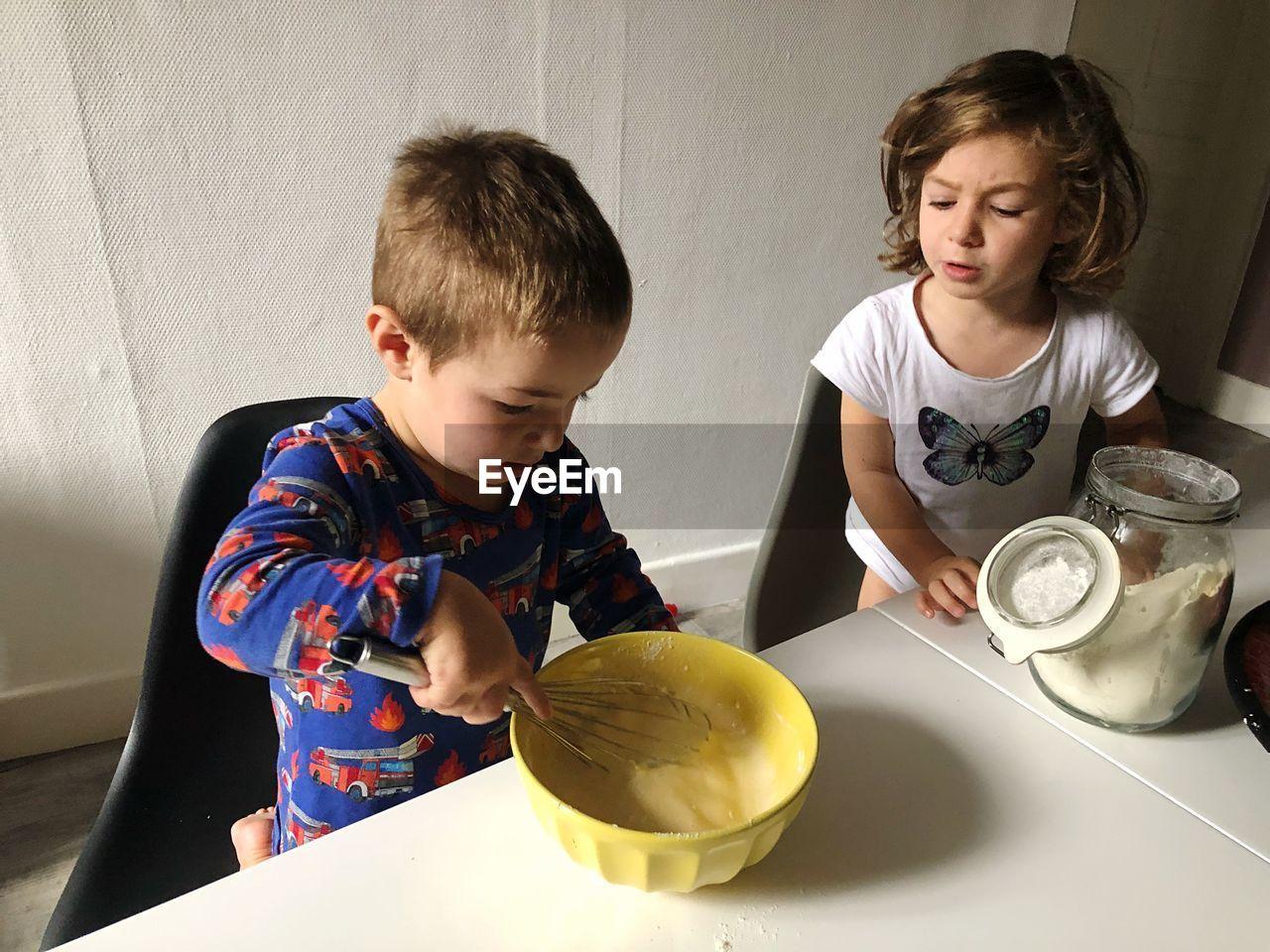 Cute siblings preparing food in kitchen