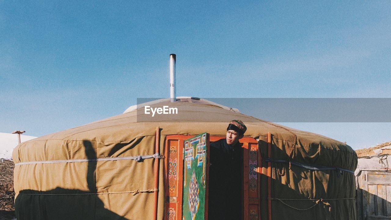 View of man in doorway of yurt