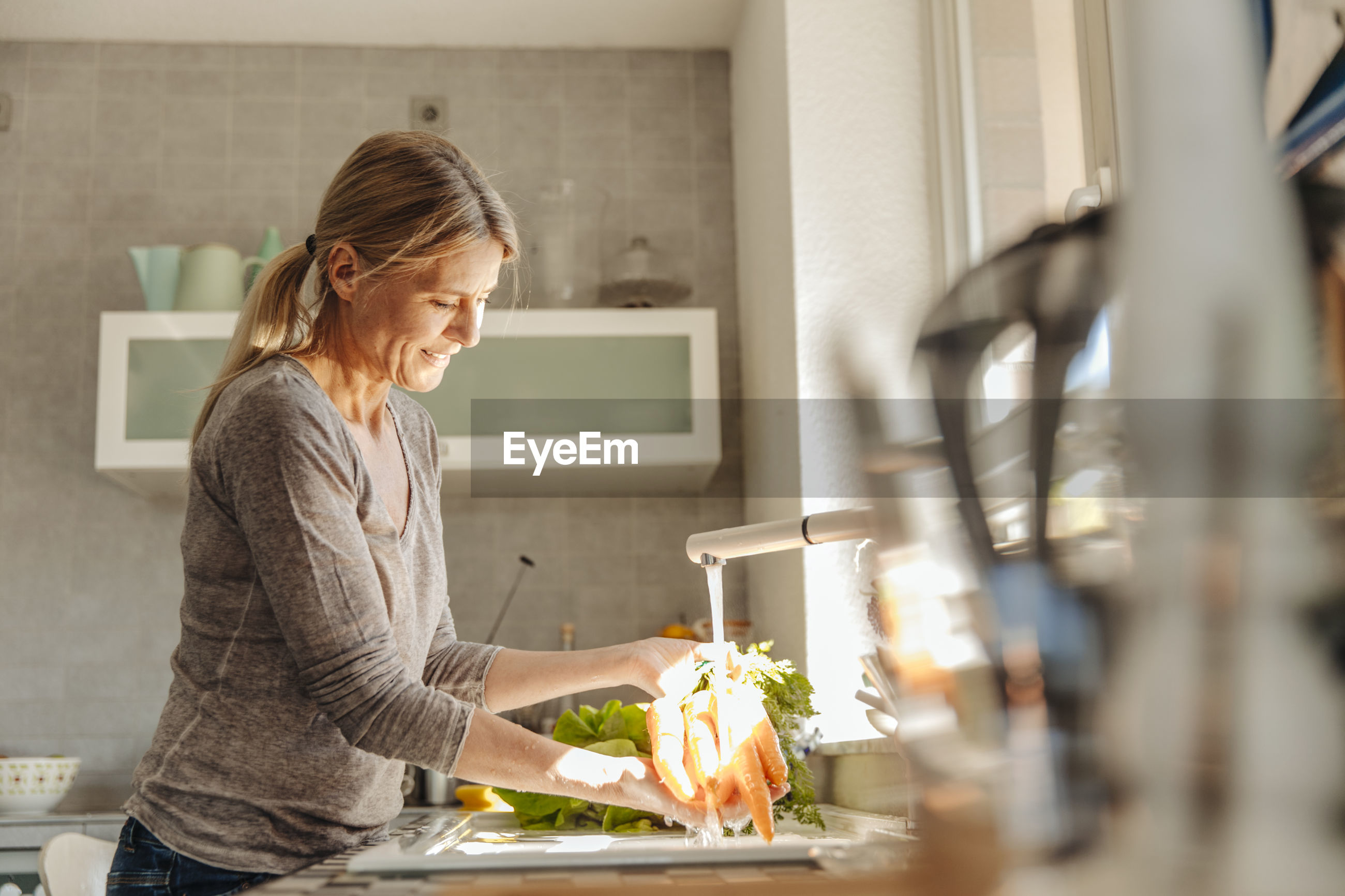 SIDE VIEW OF WOMAN STANDING IN FRONT OF KITCHEN