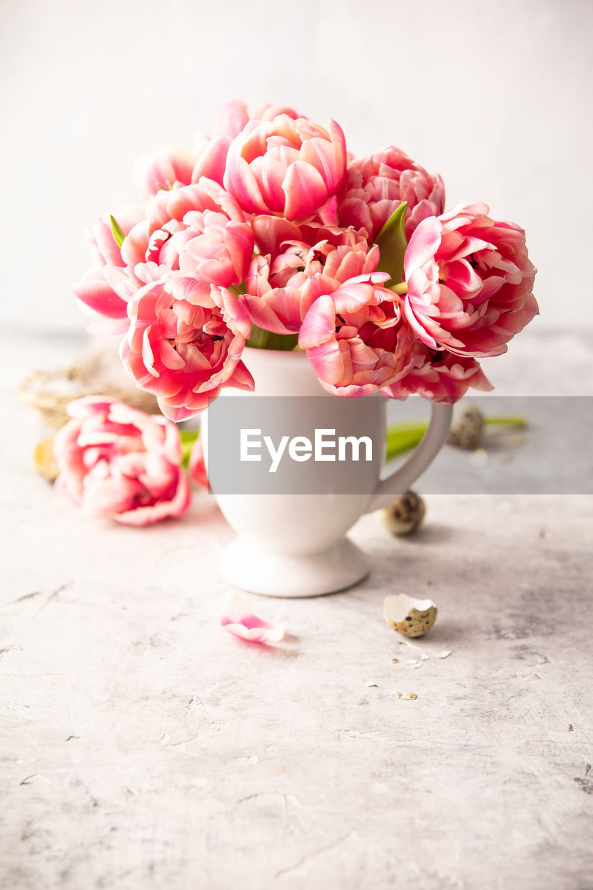 flower, flowering plant, plant, beauty in nature, freshness, pink color, fragility, petal, vulnerability, close-up, table, nature, indoors, flower head, no people, inflorescence, still life, vase, rose, focus on foreground, bunch of flowers, flower arrangement, crockery