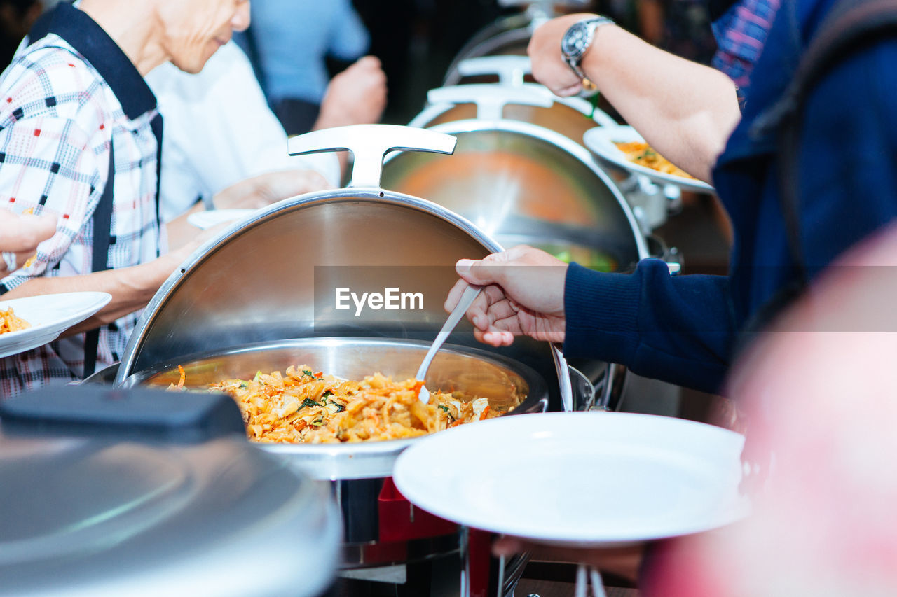 Close-Up Of People Serving Food In Restaurant