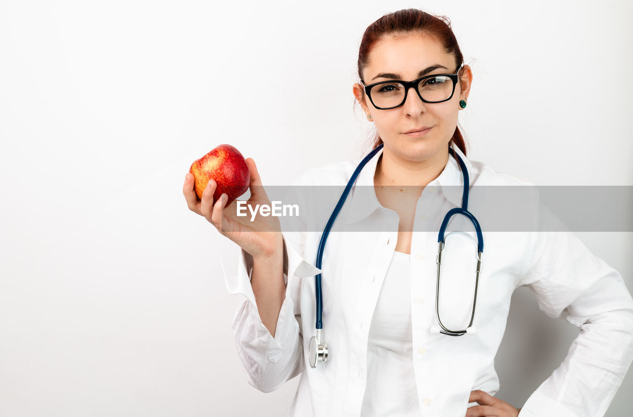 medical instrument, stethoscope, healthcare and medicine, medical supplies, medical equipment, doctor, indoors, occupation, eyeglasses, adult, glasses, professional occupation, lab coat, holding, apple - fruit, expertise, fruit, wellbeing, studio shot, clothing, care