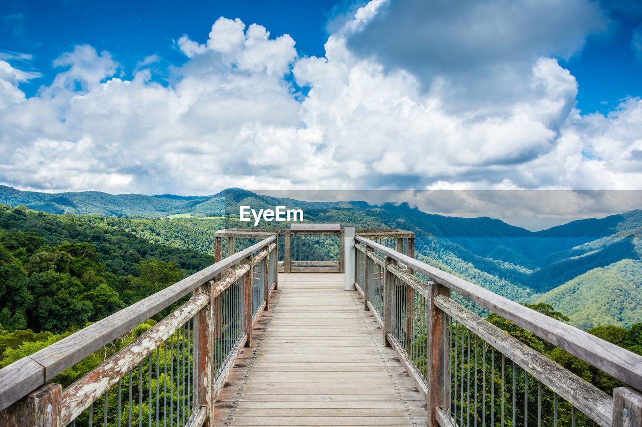 Boardwalk Leading Towards Mountain Against Sky