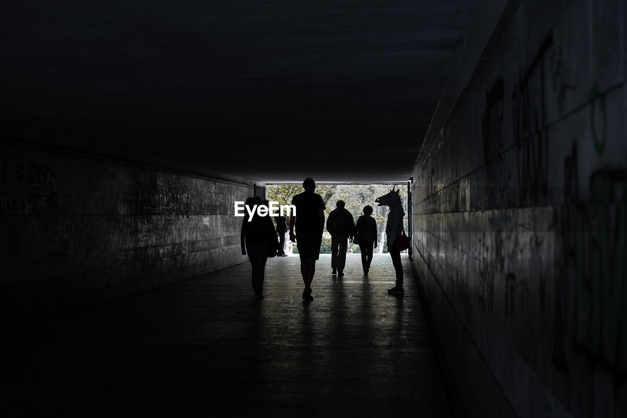 architecture, tunnel, walking, silhouette, built structure, group of people, men, light at the end of the tunnel, people, wall - building feature, the way forward, real people, women, direction, dark, indoors, lifestyles, building, adult, full length, underpass
