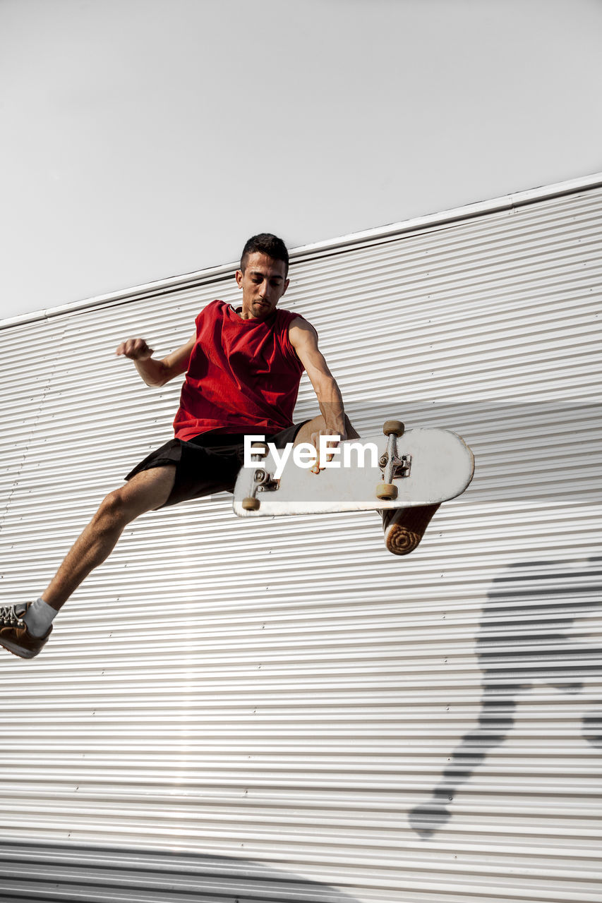 Man with skateboard in mid-air against wall