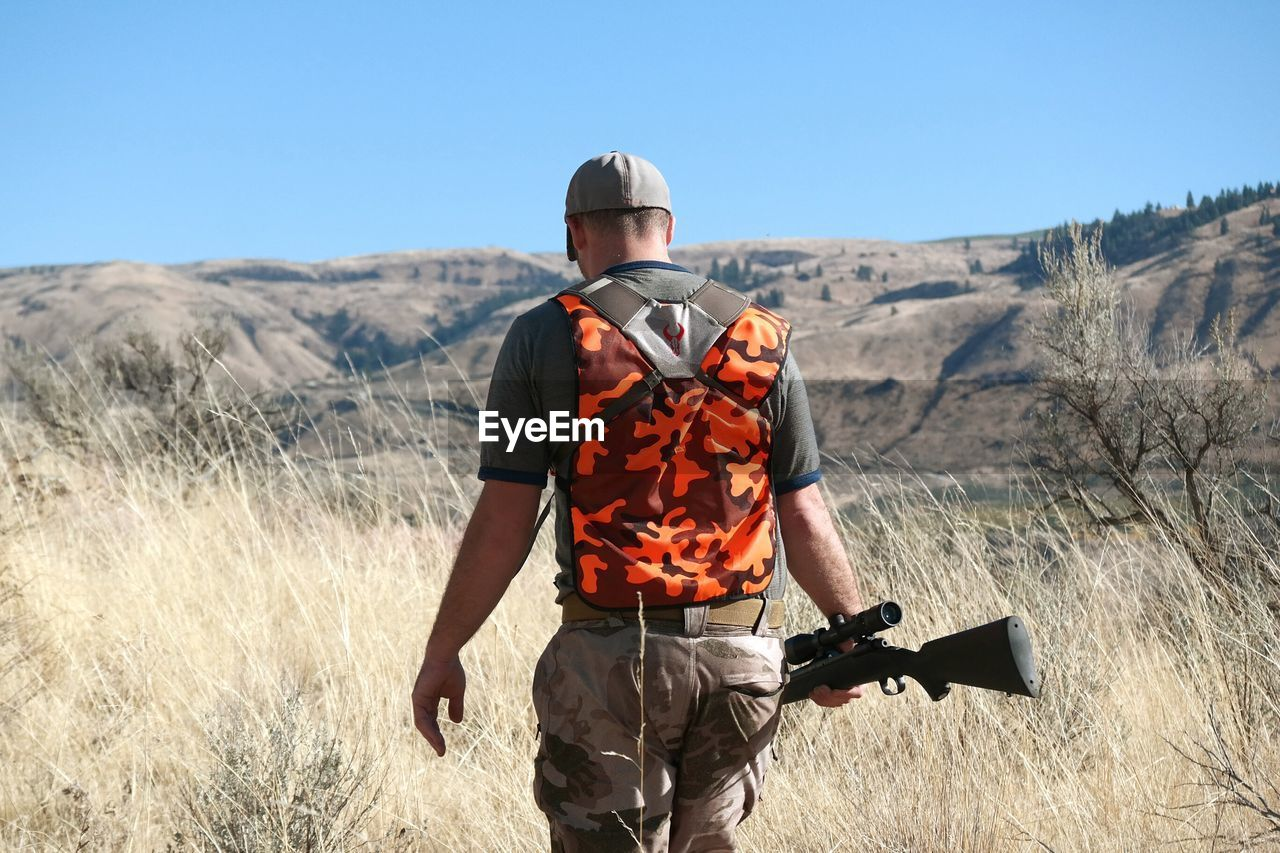 Rear View Of Man With Sniper Standing On Field Against Clear Sky