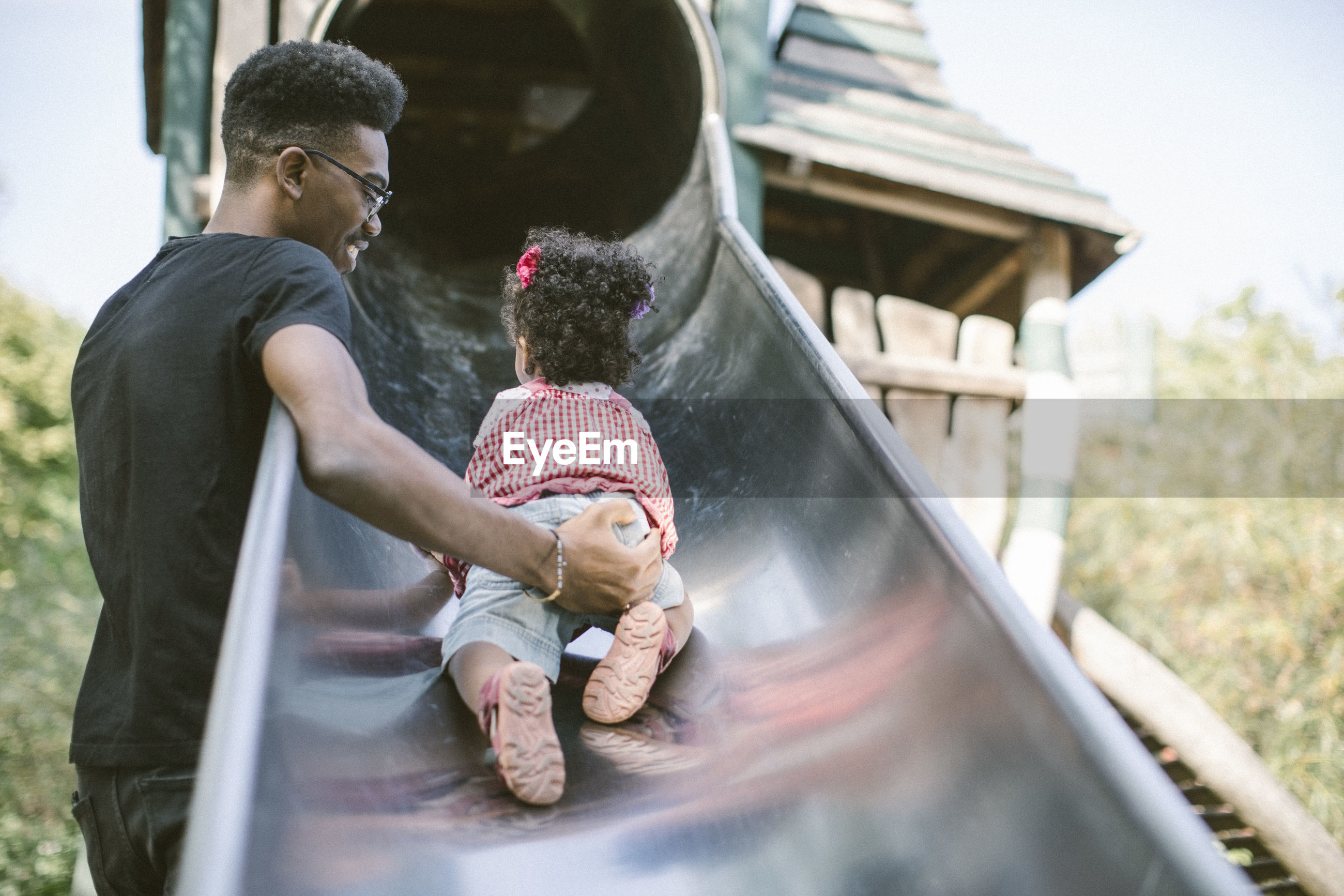 Father supporting daughter crawling up on slide at playground