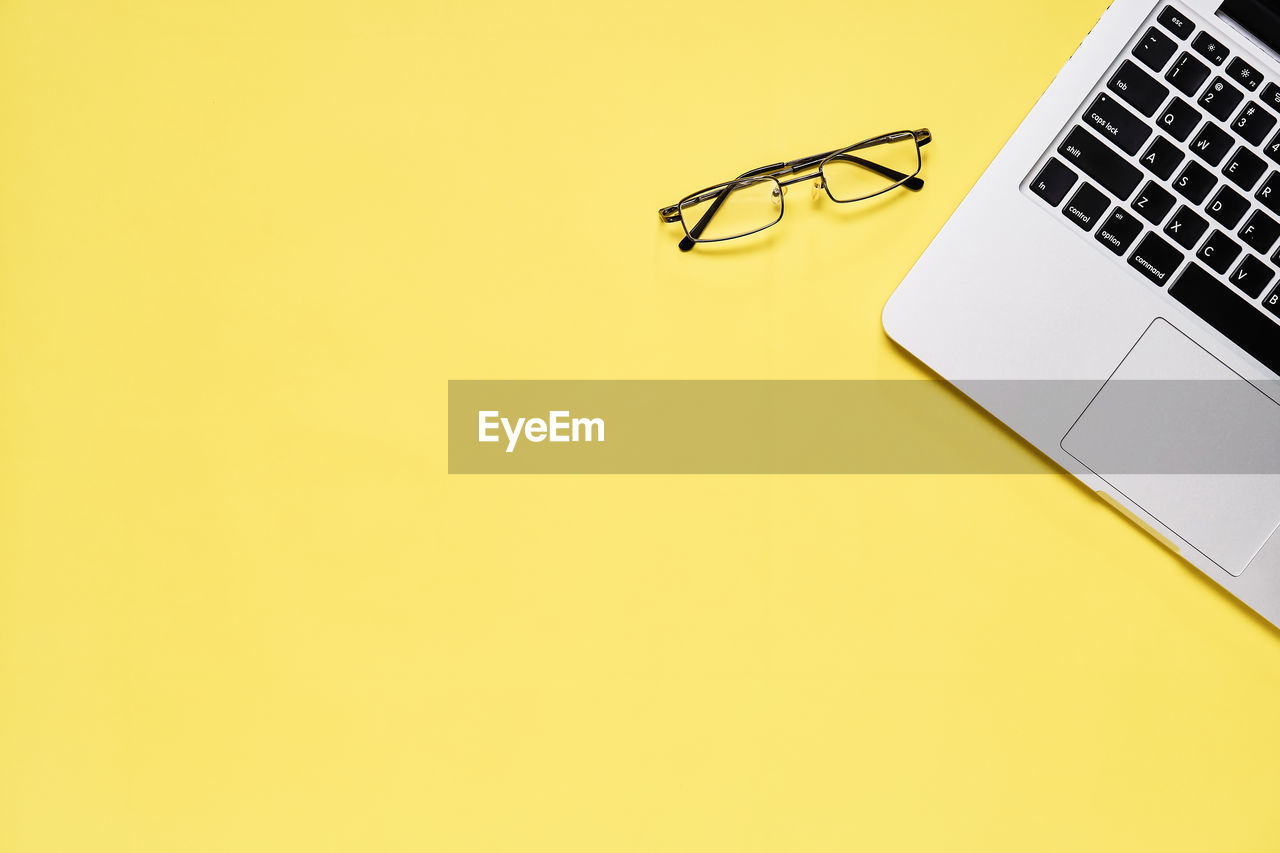 Directly Above Shot Of Laptop And Eyeglasses On Yellow Background