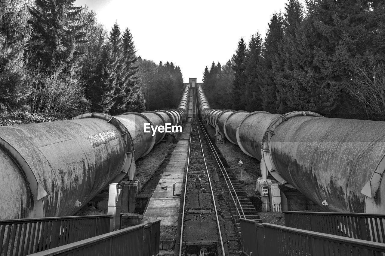 Railway Tracks Amidst Pipes And Trees Against Sky