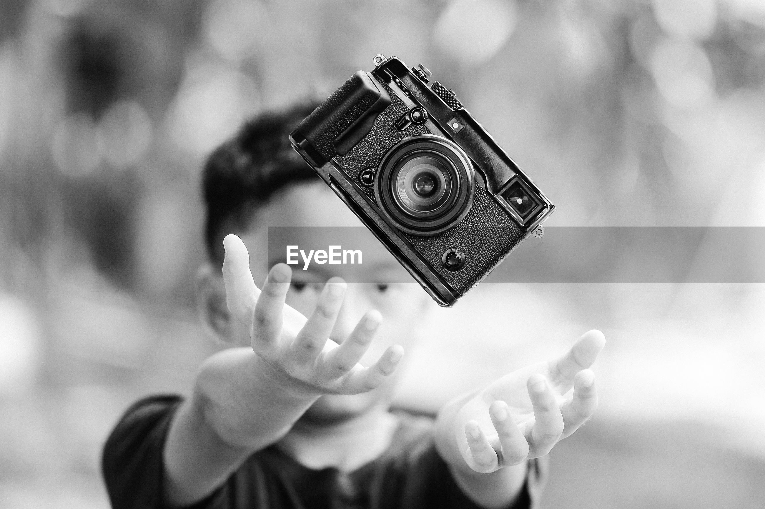 CLOSE-UP OF PERSON HOLDING CAMERA