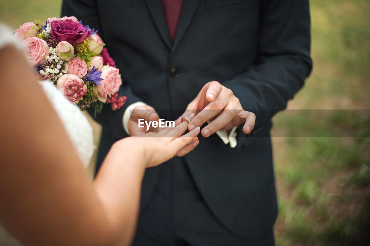 Groom Putting Wedding Ring In Finger Of Bride
