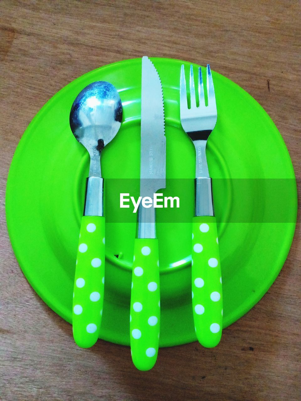 green color, still life, indoors, kitchen utensil, table, eating utensil, no people, close-up, knife, fork, high angle view, household equipment, food and drink, directly above, food, wood - material, table knife, plate, kitchen knife, plastic