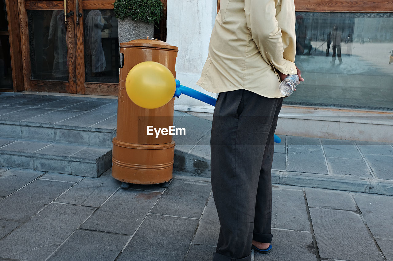 Side View Of Man With Balloon On Footpath