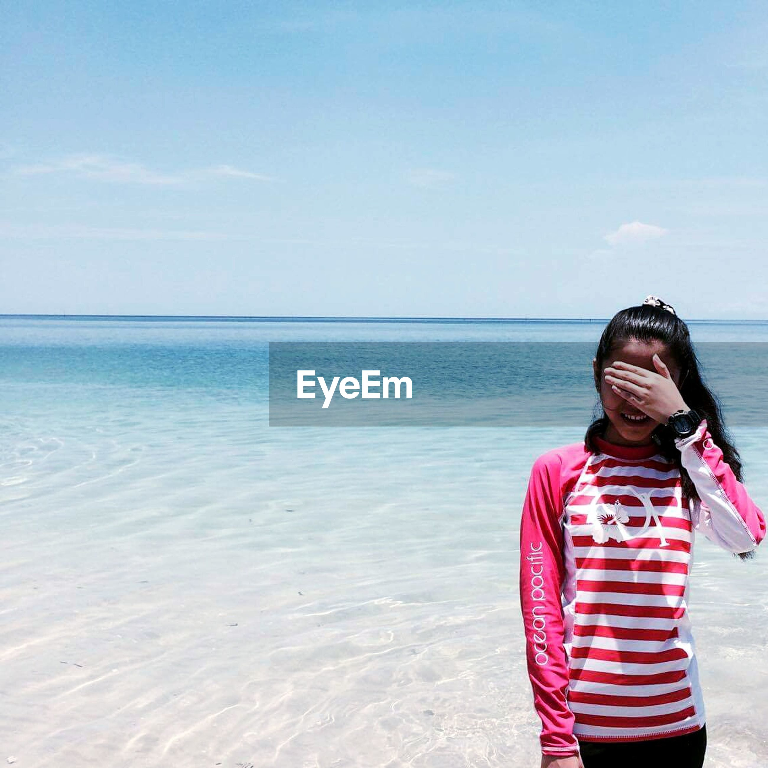 sea, one person, standing, real people, leisure activity, horizon over water, beach, sky, outdoors, lifestyles, sand, day, young women, wireless technology, scenics, young adult, water, nature, people, adult