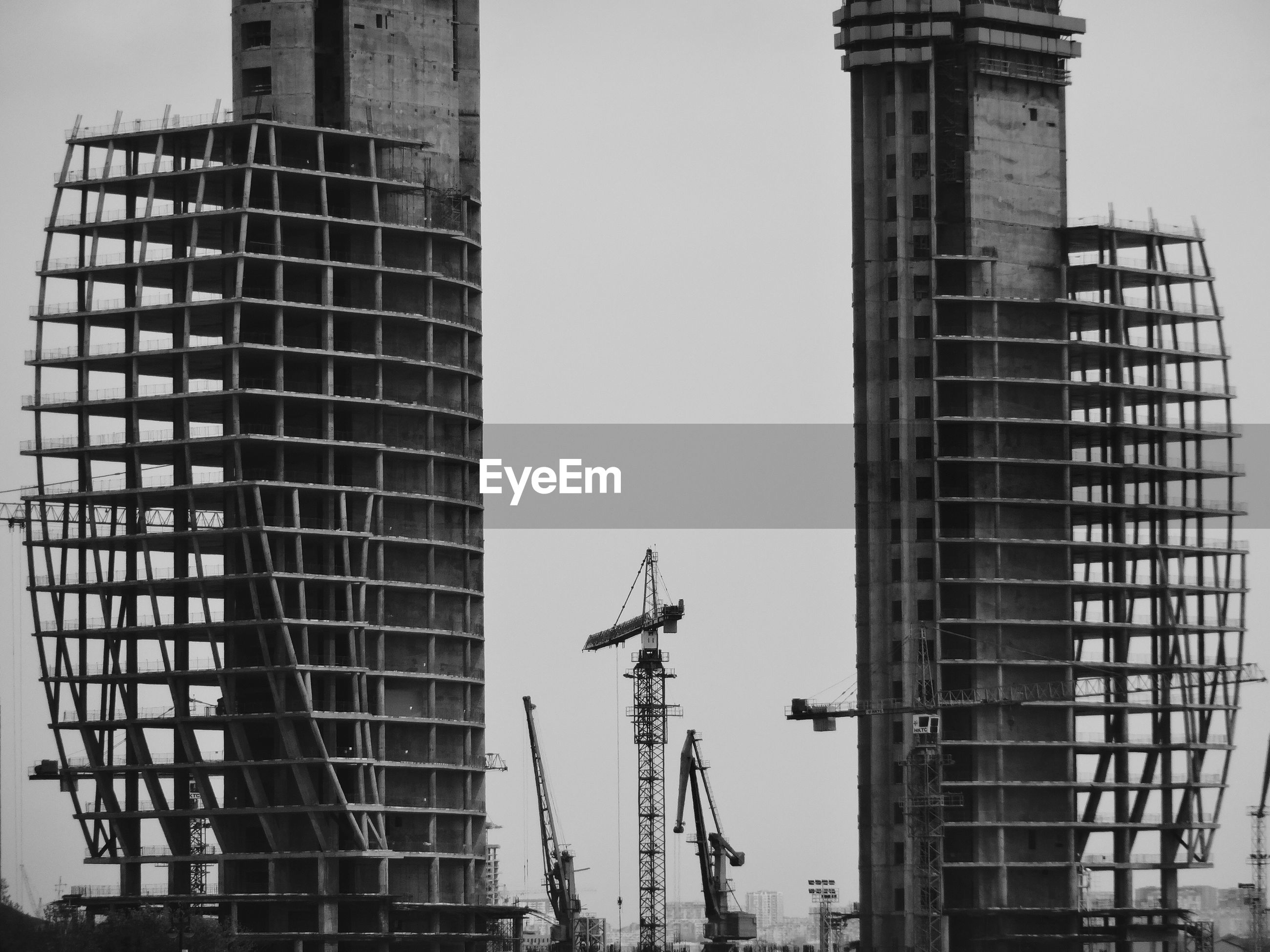 Cranes by incomplete building against sky