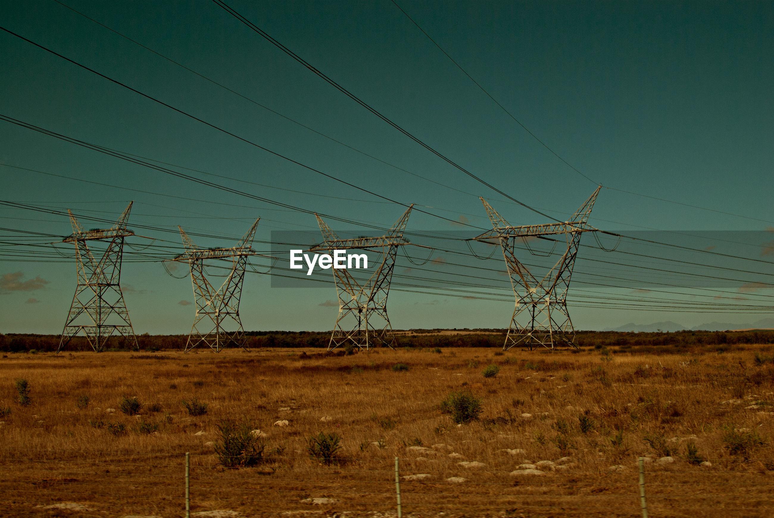 Electricity pylon on field against blue sky