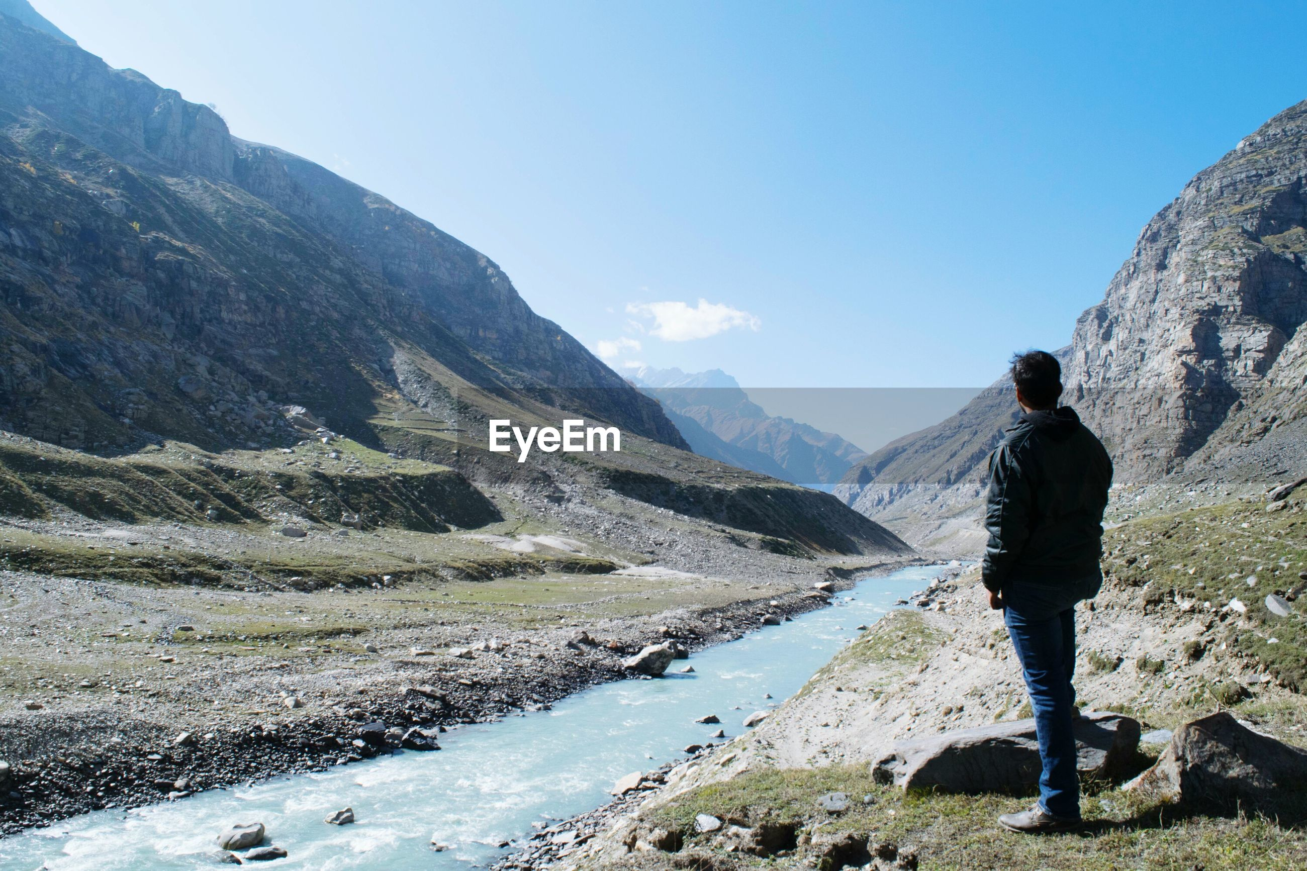 Man standing by river against mountain range