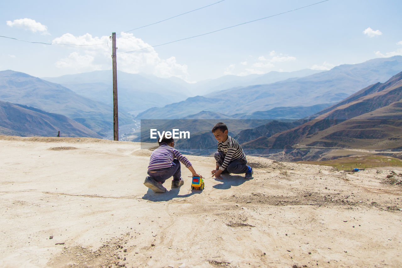 Brothers playing with toy car on mountain against sky
