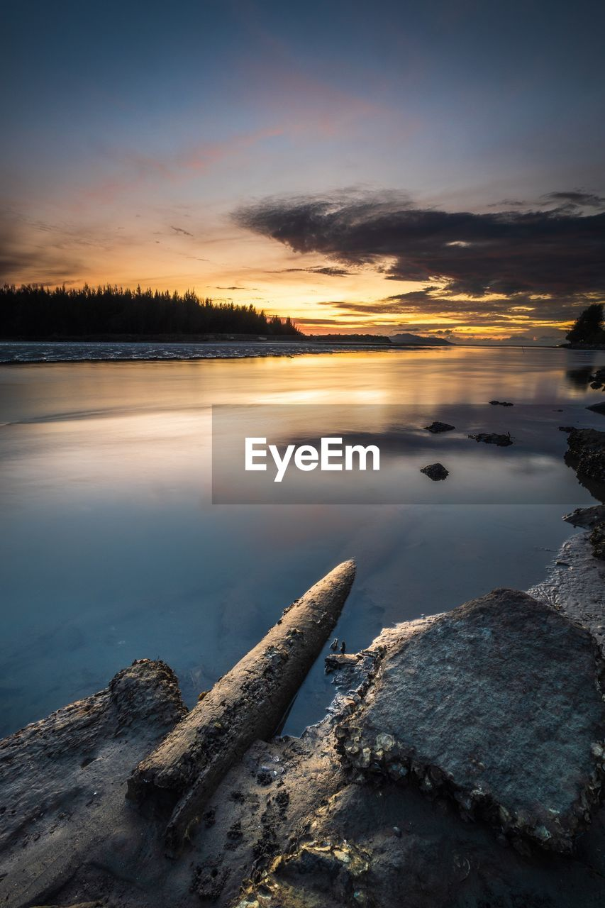 water, sky, cloud - sky, sunset, beauty in nature, scenics - nature, tranquility, tranquil scene, lake, reflection, solid, no people, rock, nature, rock - object, idyllic, orange color, non-urban scene
