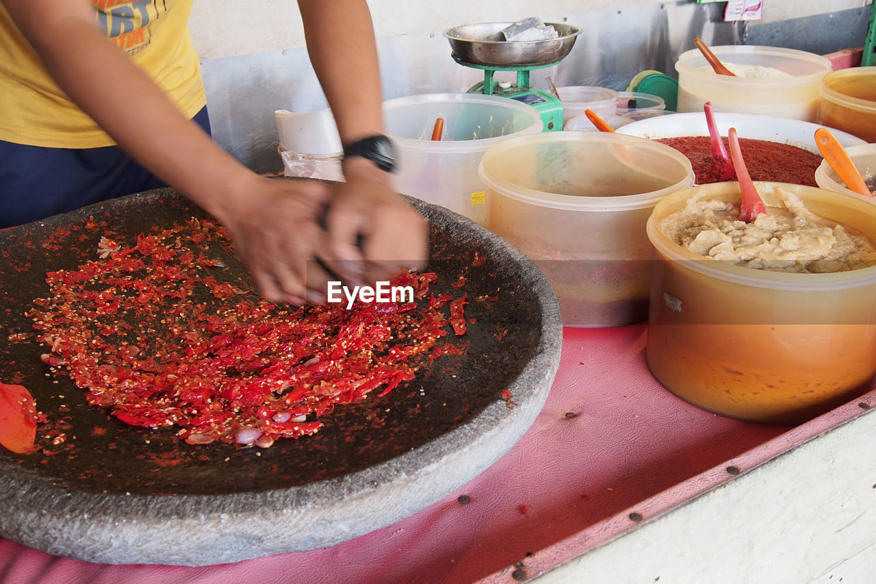 Midsection Of Grinding Red Chili Pepper In Mortar And Pestle