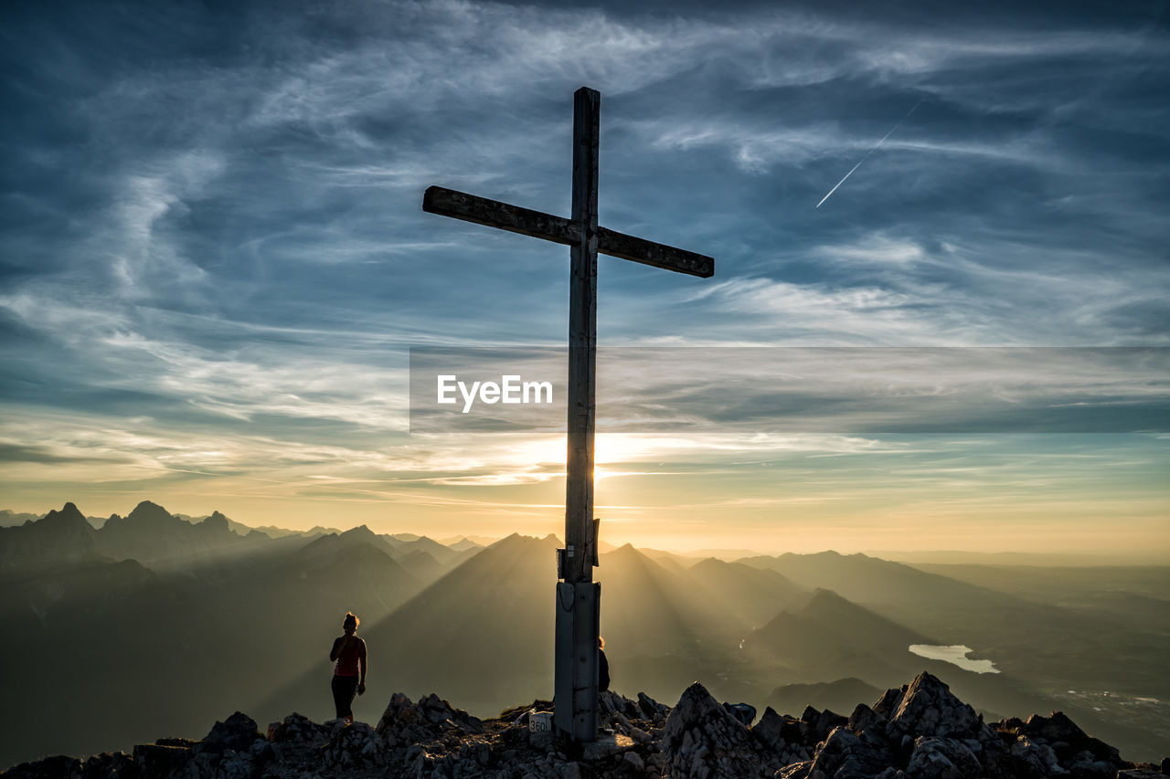 Silhouette Woman Standing By Cross On Mountain During Sunset