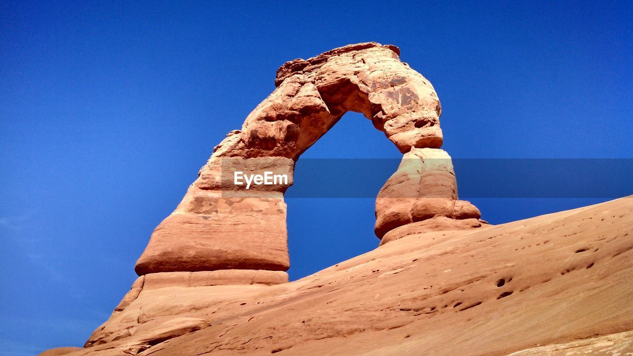 Low Angle View Of Delicate Arch Against Blue Sky At Arches National Park