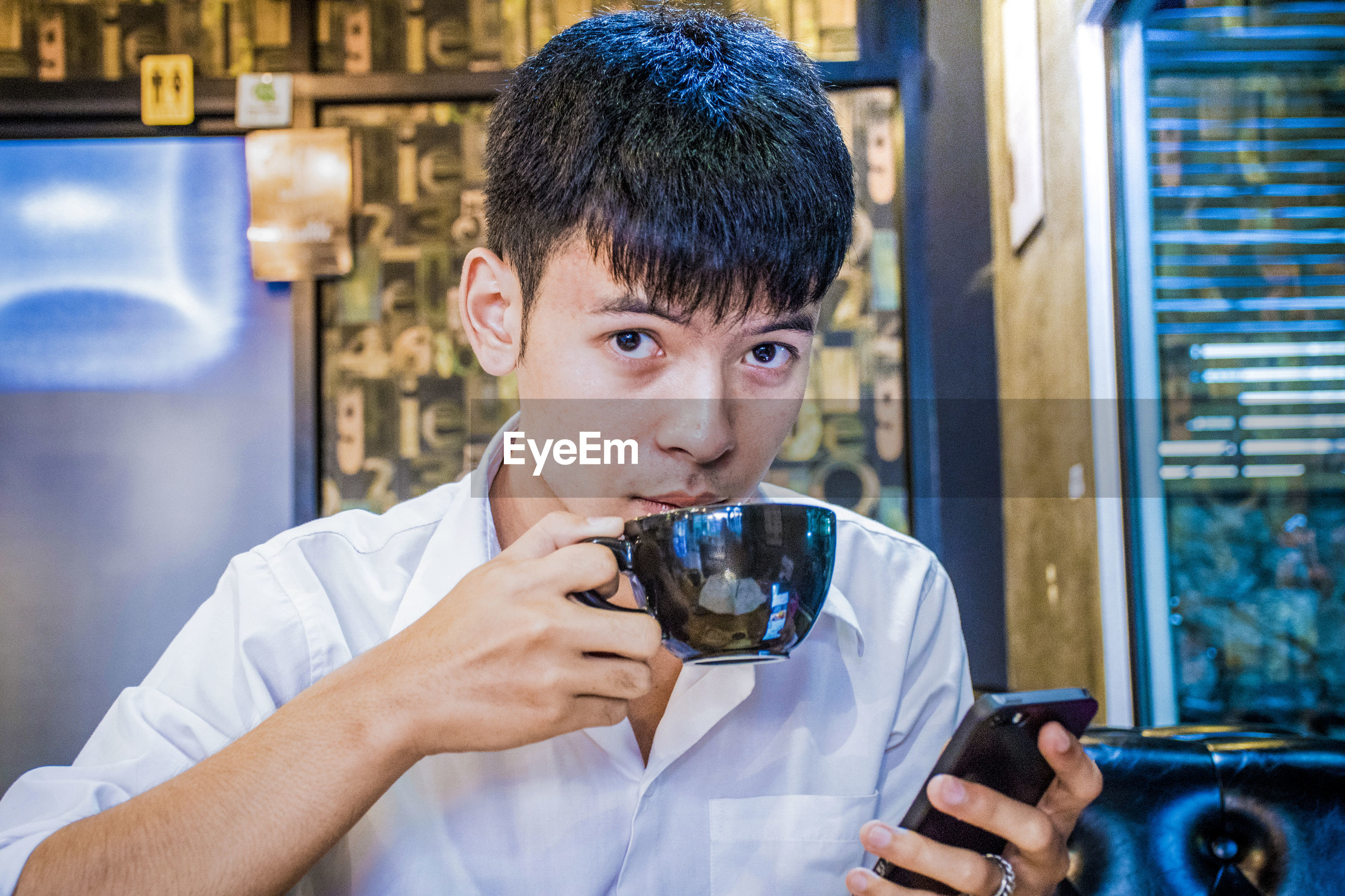 Portrait of young man drinking coffee while holding mobile phone sitting at cafe