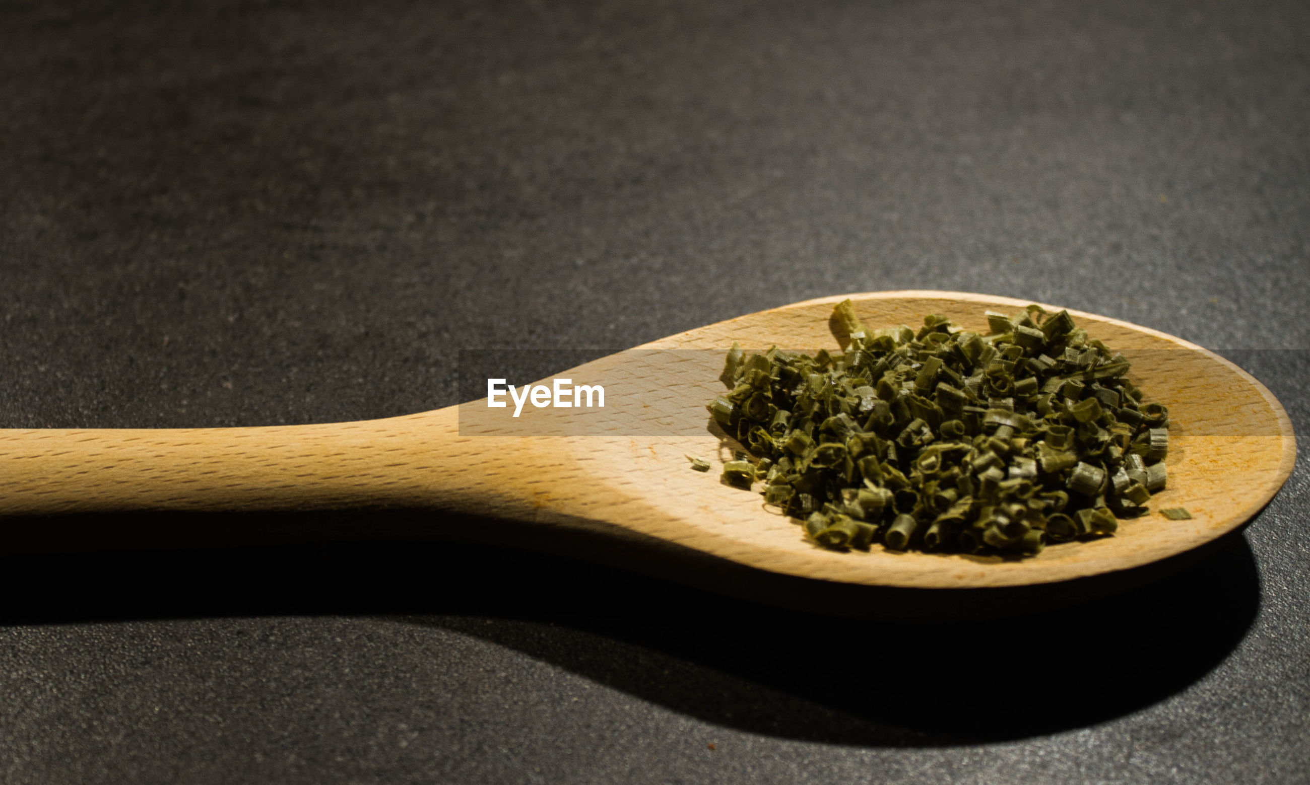Close-up of chopped chive in wooden spoon on table