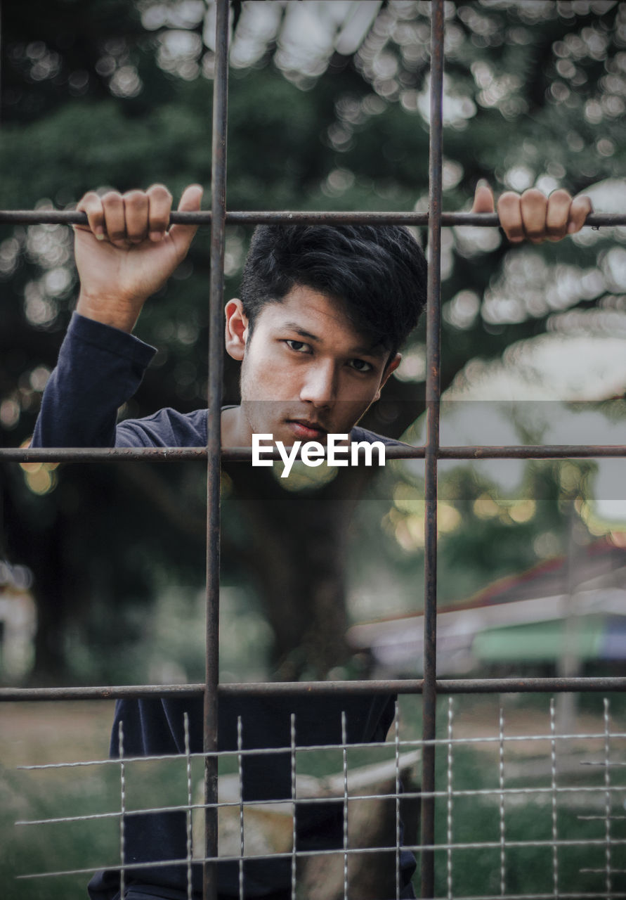 Portrait Of Young Man Behind Fence