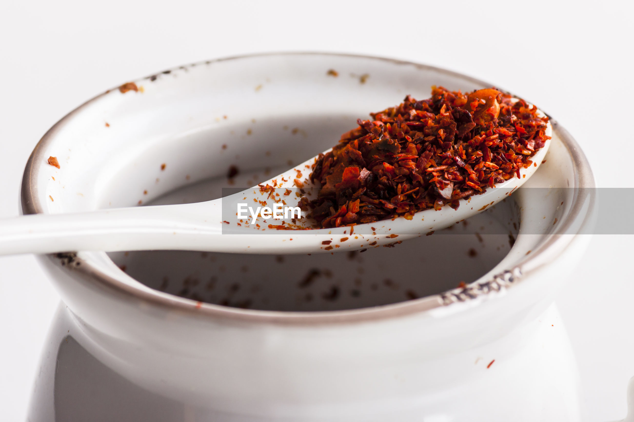 Close-up of chili flakes in spoon against white background